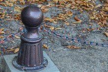 Part Of A Brown Decorative Iron Fence In A Park With A Chain And Pillar