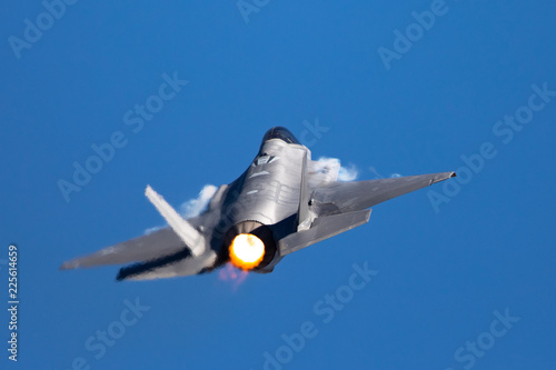fototapeta na ścianę Extremely close tail view of an F-35 Lightning II in a high G turn, with afterburner on and condensation trails at the wings root