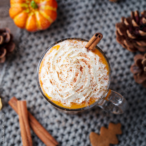 Pumpkin latte with spices and whipped cream. Grey background. Close up. Top view.