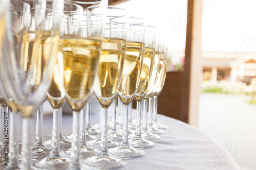 glasses with sparkling wine at an outdoor party on a sunny day