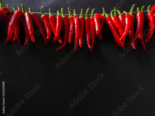 Tuinposter Hot chili peppers Red hot spicy chili pepper on the black background. A row of red hot chili peppers hanging.