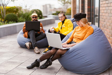 Women Use Laptop In Cafe, Relax After Work. Comfort Lounge On Bag Bean Chair.