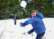 Boy In Blue Warm Coat Having Fun In Beautiful Winter Place With Snowballs