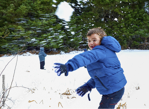 Obraz na plátně Boy in blue warm coat having fun in beautiful winter place with snowballs