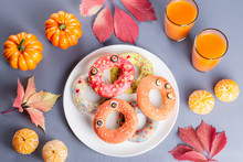 Halloween Donuts With Pumpkin Juice And Autumn Leaves.