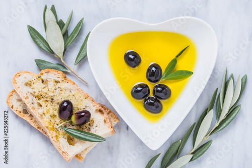 Olive oil, olives and bread on white marble.Testing fresh extra virgin olive oil.