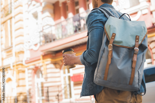 Obraz cropped shot of young man with backpack and coffee to go walking by street - fototapety do salonu