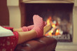 Woman feet with socks sitting near fireplace with a warmth background. Woman in warm socks resting near fireplace at home with book. Toning