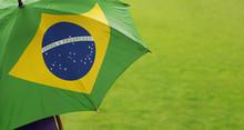 Brazil Flag Umbrella. Close Up Of Printed Umbrella Over Green Grass Lawn / Field. Rainy Weather Forecast Concept.