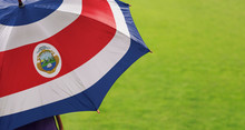 Costa Rica Flag Umbrella. Close Up Of Printed Umbrella Over Green Grass Lawn / Field. Rainy Weather Forecast Concept.