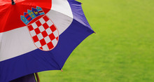 Croatia Flag Umbrella. Close Up Of Printed Umbrella Over Green Grass Lawn / Field. Rainy Weather Forecast Concept.