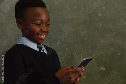 Schoolboy using mobile phone near chalkboard