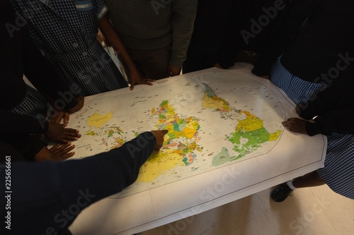 Schoolkids looking at world map in classroom