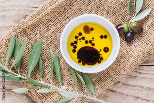 Olive oil and vinegar on wooden background.