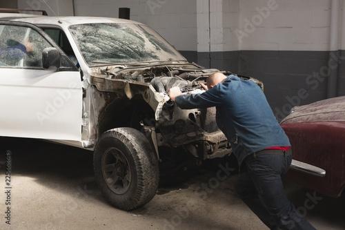 Mechanic pushing car in garage