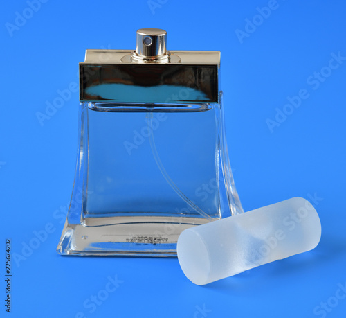 transparent bottle with toilet water on blue background Canvas Print