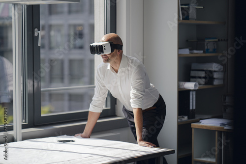 Businessman standing in his office, using VR glasses