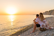 Young Couple In Love, Man And Woman Enjoying Romantic Evening On The Beach Watching The Sunset