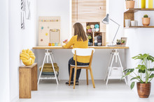 Woman Sitting At A Desk In A H...