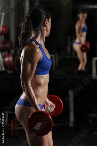 Close up through the mirror of a fit woman lifting weights Canvas Print