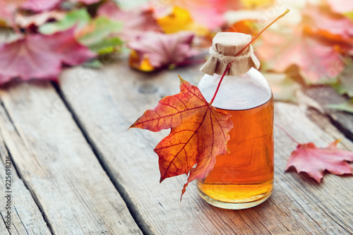 Maple syrup or healthy tincture and fallen maple leaves. Canvas