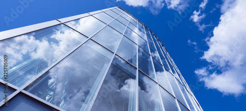 Spoed Foto op Canvas Stad gebouw modern blue glass and metal office facade reflects clouds and blue sky