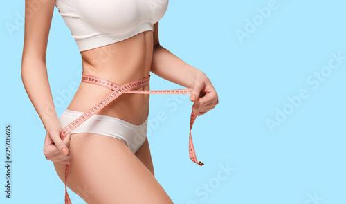 Fotografía  The girl taking measurements of her body, blue studio background.