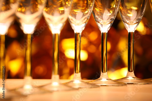 Foto op Plexiglas Alcohol Empty champagne glass gold bokeh studio