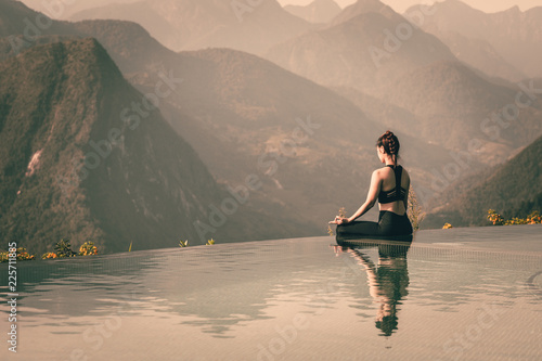 Poster Ecole de Yoga Beautiful Attractive Asian woman practice yoga Lotus pose on the pool above the Mountain peak in the morning in front of beautiful nature views,Feel so comfortable and relax in holiday,Warm Tone