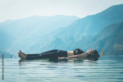 Fotobehang Ontspanning Beautiful Attractive Asian woman practice yoga Dead Body or Savasana on the pool above the Mountain peak in the morning in front of beautiful nature views in SAPA vietnam,Feel so comfortable
