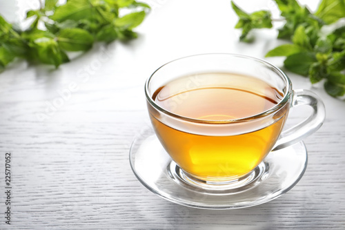 Cup with hot aromatic mint tea on table