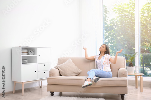 Obraz Young woman relaxing under air conditioner at home - fototapety do salonu