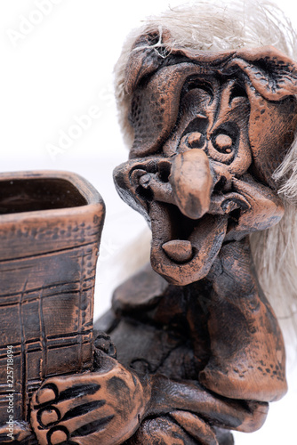 Fotografie, Obraz  Old smiling witch sitting on the chimney  isolated on white background
