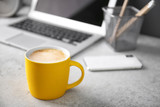 Yellow cup with coffee on office table. Space for text