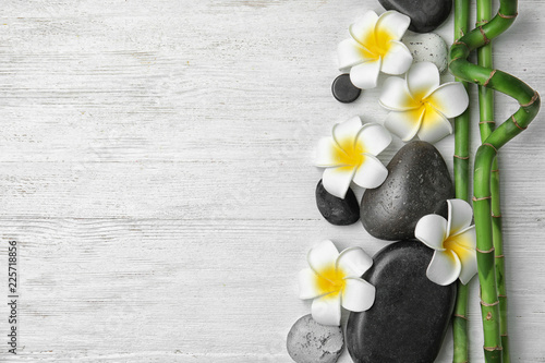 Flat lay composition with bamboo branches and spa stones on wooden background. Space for text