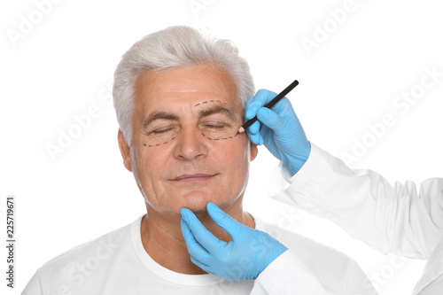 Photo Doctor marking senior man face before cosmetic surgery on white background