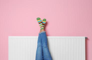 Woman warming legs on heating radiator near color wall