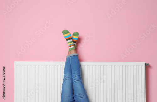Woman warming legs on heating radiator near color wall