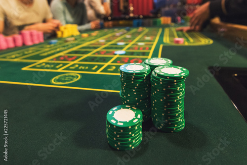 фотография  Casino, gambling and entertainment concept - stack of poker chips on a green tab