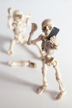 Skeleton Figures With Broken Leg Whilst Taking A Selfie With Phone