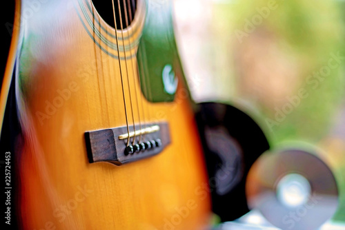 In de dag Muziekwinkel brown acoustic guitar, close-up, guitar part and CD