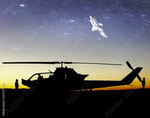Spaceship flying into outer space. Space travel. Silhouette of helicopter and people at sunset. Air tourism. Some elements of this image are furnished by NASA