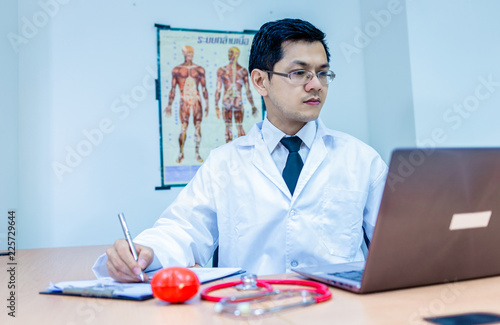Fotografie, Obraz  Doctor and his table in the office with stethoscope, miniature heart, laptop and smart phone