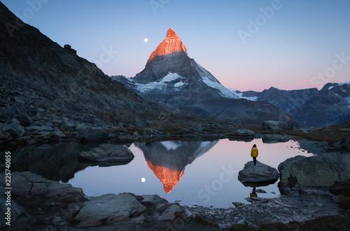 Foto auf Gartenposter Gebirge A girl on a rock in the Riffelsee watching the first sunlight shining on the Matterhorn.