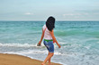 a young girl in a white Tshirt is walking along the sand in the sea. brunette on the shore of the azure sea in Bulgaria, golden sands
