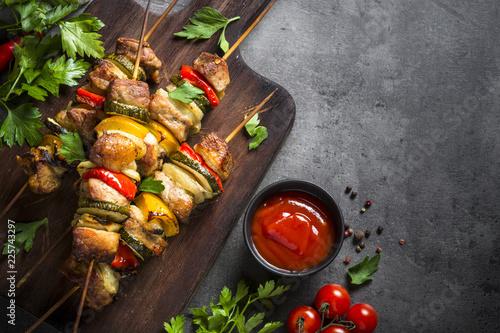 Grilled shish kebab with vegetables on black.
