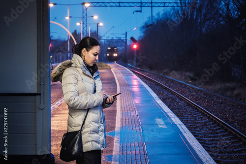 In de dag Tunnel A woman is wating for a train and uses a smartphone at a railway station