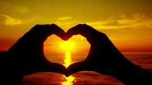 Loop Of Ocean Sunset Shining Through Heart Shaped Hands