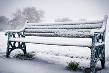 Snow-covered Vintage Wooden Bench At Winter.
