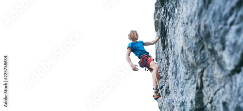 male rock climber resting while climbing the challenging route on the rocky wall
